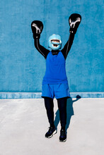Full Length Smiling Mature Female In Sportswear And Boxing Gloves Standing With Helmet Against Blue Wall With Arms Raised