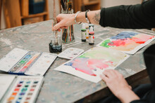 Crop Unrecognizable Female Artist Painting With Watercolors On Paper While Sitting At Table In Art Studio