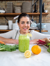 Cheerful Female Looking At Camera At Table With Jar Of Delicious Vegan Smoothie And Fresh Citrus Fruits In Kitchen