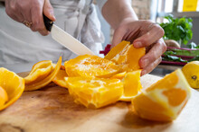 Crop Unrecognizable Female Cutting Ripe Juicy Oranges With Knife On Wooden Chopping Board At Kitchen Table