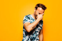 Cheerful Adult Bearded Male Model With Stylish Haircut Wearing Trendy Summer T Shirt With Tropical Foliage Print Covering Face With Eyes Closed Against Yellow Background
