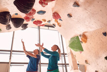 Low Angle Of Male And Female Climbers Practicing In Bouldering Center Near Climbing Wall