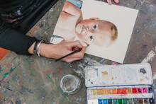 Crop Female Artist In Apron Painting With Watercolors On Paper While Sitting At Table In Creative Workshop