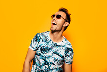 Cheerful Adult Bearded Male Model With Stylish Haircut And Sunglasses Wearing Trendy Summer T Shirt With Tropical Foliage Print Looking Away Against Yellow Background