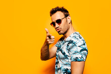 Side View Of Stylish Adult Unshaven Male Model In Trendy T Shirt With Tropical Print And Sunglasses Pointing At Camera Against Bright Yellow Background