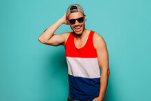 Cheerful Young Bearded Ethnic Guy Wearing Trendy Casual Striped Shirt And Cap With Black Sunglasses Touching Head And Looking At Camera On Blue Background