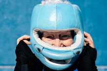 Content Mature Female In Activewear Boxing Helmet And Hand Wraps Raising Hands Near Head Against Blue Wall And Looking At Camera