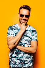 Cheerful Adult Bearded Male Model With Stylish Haircut And Sunglasses Wearing Trendy Summer T Shirt With Tropical Foliage Print Looking At Camera Against Yellow Background