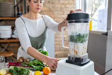 Crop Female Blending Chard Leaves With Vegetarian Milk In Kitchen Appliance While Preparing Healthy Drink In House