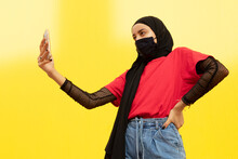 From Below Of Cool Ethnic Female In Headscarf With Hand On Hip Taking Self Portrait On Cellphone On Yellow Background