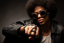 Trendy African American Male In Leather Jacket And Contemporary Sunglasses With Afro Hairstyle On Gray Background