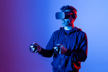 Anonymous Unshaven Male In Hoodie And Modern Goggles With Controllers And Extended Arm Experiencing Virtual Reality