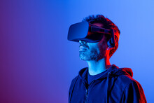 Unrecognizable Bearded Male In Hoodie And Modern Headset Exploring Virtual Reality In Neon Light