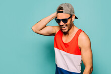 Cheerful Young Bearded Ethnic Guy Wearing Trendy Casual Striped Shirt And Cap With Black Sunglasses Touching Head And Looking Away On Blue Background