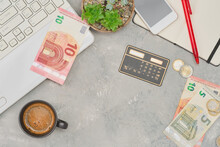 Euro Banknotes And Coins On Gray Concrete Table, Mock Up With Copy Space. The Idea Of planning Purchases And Paying Taxes, Laptop And Calculator For Accounting Payments. Espresso Cup