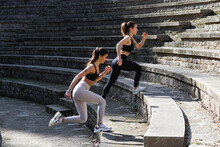 Side View Of Fit Females In Activewear Doing Exercises And Stepping On Stone Stairs While Warming Up Before Yoga Session
