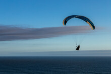 Bay Area Paraglider Soaring Over Pacific Ocean At Sunset