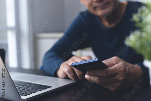 Asian man using mobile phone during online working on laptop computer from home office - fototapety na wymiar