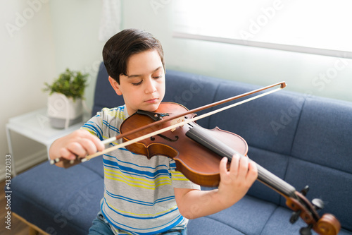 Fototapeta Little student practicing a song on the violin