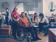 Leinwandbild Motiv Disabled businessman in a wheelchair at work in modern open space coworking office with team