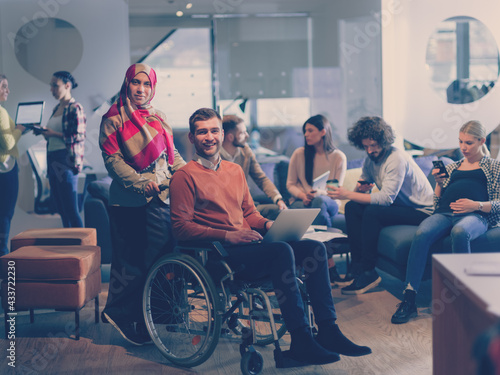 Fototapeta Disabled businessman in a wheelchair at work in modern open space coworking office with team obraz