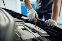 Close-up Of Mechanic Examining Car Oil  At Auto Repair Shop.