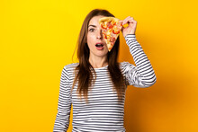 Surprised Young Woman Covering Her Eyes With A Slice Of Fresh Pizza On A Yellow Background