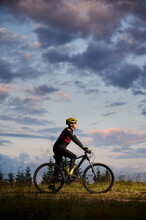 Vertical Snapshot Of Man Cyclist Riding Bike On Sunset In The Mountains. Bicyclist Wearing Helmet, Sports Glasses And Uniform. Side View. Evening Sky On Background. Concept Of Active Lifestyle
