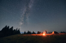 Man Hiker Standing On Grassy Hill Near Campfire And Pointing Finger At Beautiful Night Starry Sky With Milky Way Under Mountain Valley. Concept Of Hiking, Night Camping And Astrology.
