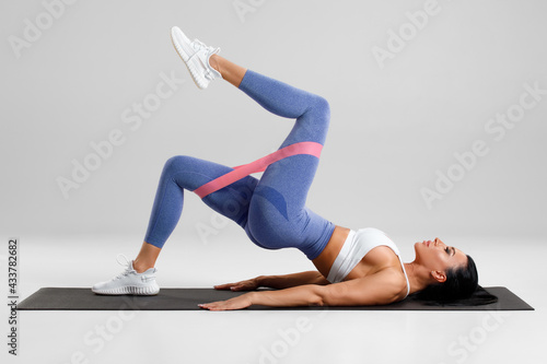 Obraz na płótnie Fitness woman doing glute bridge exercise with resistance band on gray background