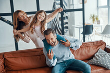 Cheerful Young Family Bonding Together While Sitting On Sofa At Home