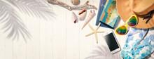 白いウッドデッキの上にある麦わら帽子、サングラス、ビーチサンダルなど夏のリゾートのイメージ。もしくは海外旅行のイメージ。真上からのアングル
