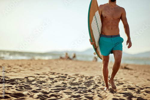 Young handsome male surfer holding a surfboard and walking the beach at sea. Summer, vacation, sea #433790231