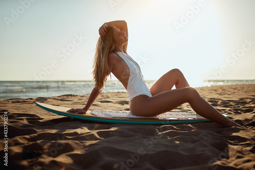 Young sexy girl is sitting on a surfboard and sunbathing at the beach at sea. Summer, vacation, sea #433790274
