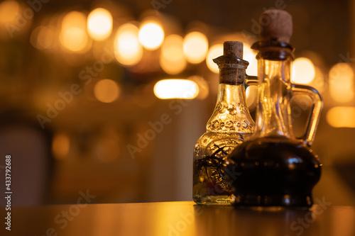Billede på lærred Two curly glass bottles with wooden corks  with balsamic vinegar, oil, dark brown, black sauce on the table in a italian restaurant, cuisine, cafe