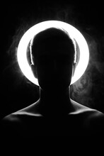 Silhouette Of A Man Against The Background Of A Shining Halo. Beautiful Collarbone In Black And White In