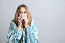 Young Woman With Blanket Suffering From Runny Nose On Light Background. Space For Text