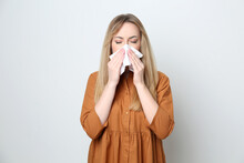 Young Woman With Tissue Suffering From Runny Nose On White Background