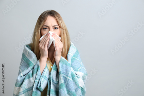 Young woman with blanket suffering from runny nose on light background Fototapet