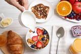 Fototapeta Kawa jest smaczna - Man pouring greek yoghurt into granola at white wooden table, top view
