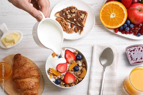 Man pouring greek yoghurt into granola at white wooden table, top view - fototapety na wymiar