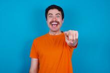 Excited Positive Young Handsome Caucasian Man With Moustache Wearing Orange T-shirt Against Blue Background Points Index Finger Directly At You, Sees Something Very Funny. Wow, Amazing