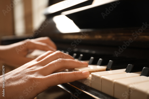 Obraz na plátně Young woman playing piano, closeup. Music lesson
