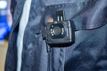 Small DVR Is Attached To Shirt. Chest Video Recorder On Background Of Uniform. It Is Attached To A Worker Uniform. Recording Equipment On Worker's Clothing. Portable Device For Video Recording.