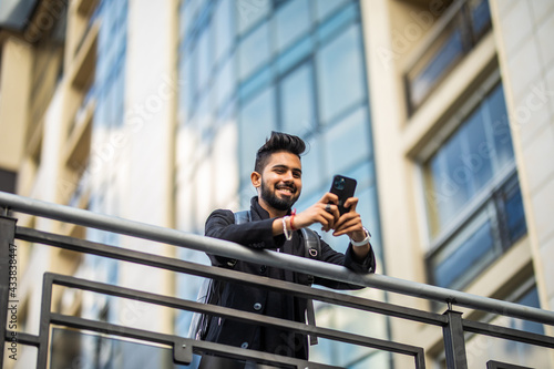 Foto The Attractive Well-dressed Businessman Is Leaning On The Handrail And Holding The Phone In His Hands