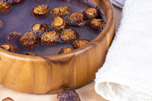 Brown Dry Soap Nuts (Soapberries, Sapindus Mukorossi) In The Water With The Towel For Organic Laundry And Gentle Natural Skin Care On Light Background.