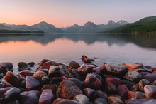 Close Up Of The Giant Colorful Pebbles Of Lake McDonald With The Towering Rocky Mountain Peaks, Lake Reflections And A Colorful Pink, Orange Sunset At Glacier National Park, Montana, USA.