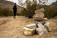 Cairn Stands Along Side Of Trail As Hiker Passes By