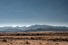 Dry Grass Across Brown Field Below Mountains In Nevada
