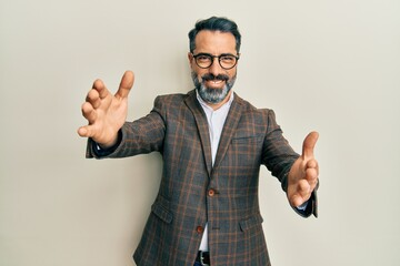 Middle age man with beard and grey hair wearing business jacket and glasses looking at the camera smiling with open arms for hug. cheerful expression embracing happiness.